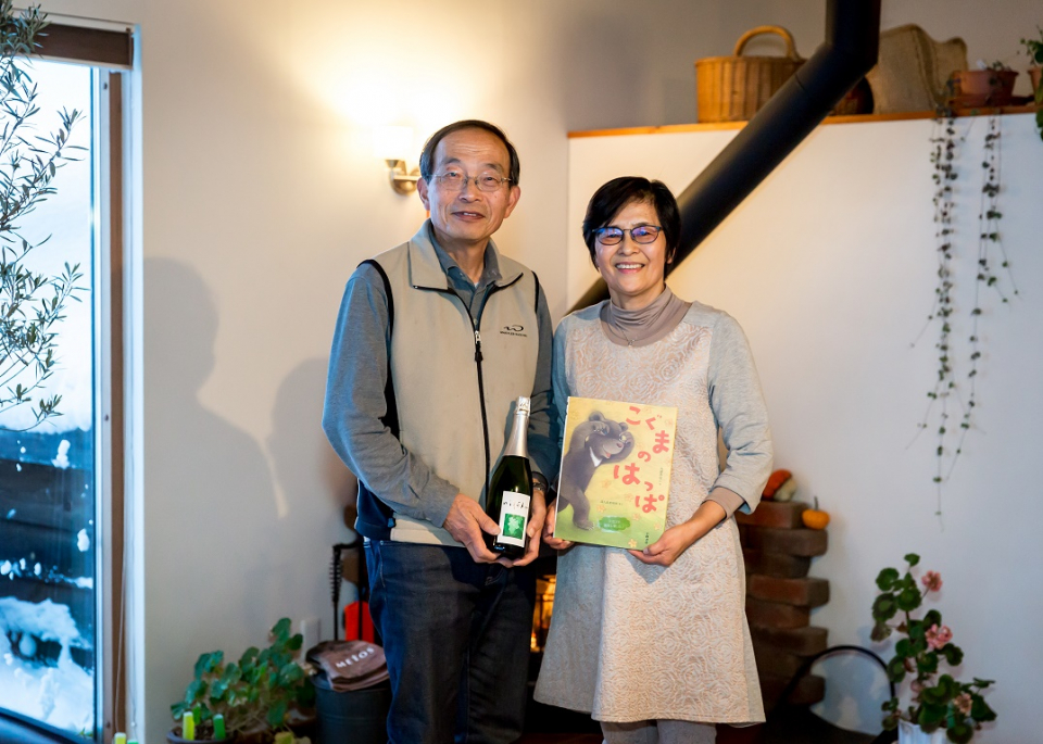 Honma san couple with wine and picture book in hand